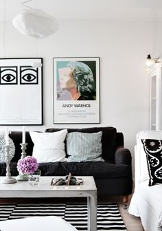 Black couches, white table, pastel and white cushion, brighter colours on table and in art