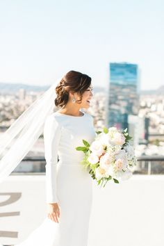"""Simple, clean, modern, and fun. That's the vibe these two Los Angles lovies were going for, and we say """"mission accomplished."""" They chose theAT&T Centeras their venue, and the rooftop views (including their first look on ahelipad!) perfectly set the scene.Ruth Eileencame"""