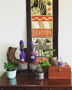 African corner of our living room with Cameroonian dolls, shell necklace and South African textile.