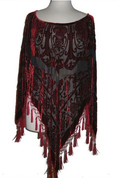 Vibrant red Pancho in a burnout velvet silk and rayon mixture is adorned with rows of rayon fringe.  The scoop neck is very flattering for any figure.  The sleeves and the front and back come to a point with beatiful fringe.  A very sexy yet easy to wear pancho or top is great for any occasion.  Wear this with one of our Western Jersey pants for a Formal look or one of our Western dresses, skirts or gauchos.  For a more casual look wear it with your jeans.  The black multi has gold specs…