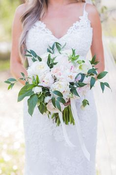 A white and blush bouquet of peonies, hydrangea, garden roses, helleborus, and greenery | Brides.com