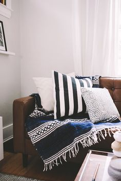 Patterned pillows and throw on a modern leather sofa, from Carla Zacharias' home tour || The Everygirl