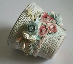 Decorated plant pot-This would be pretty wrapped with tight rolls of recycled paper, decorated with quilled flowers, and filled with dried folliage. With pretty flowers on the pot, flowers would be too much of a good thing in it.