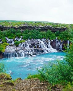 """Hraunfossar Waterfall, Iceland. Hraunfossar (meaning """"lava falls"""") is a series of waterfalls formed by rivers streaming out of the Hallmundarhraun, a lava field which flowed from an eruption of one of the volcanoes lying under the glacier Langjökull."""
