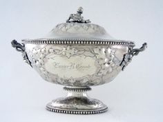 An American Coin silver tureen, mark of Jones, Ball & Co., Boston, circa 1856. Of oval form on a conforming foot, applied with beaded borders, chased with oak braches and acorns enclosing a cartouche on either side, one side engraved with a script monogram EBC, the other side Eunice B. Canale, the cast handles and finial repeating the oak branch motif; Length is 15 inches, Weight is 96.95 Troy ounces