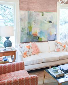 abstract art by lori glavin | blue lamp on estelle side table | floral pillows with pink accent throw on white sofa | blue print | blueprintstore.com