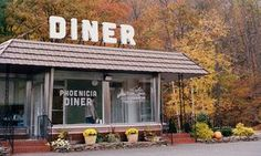 Exterior shot of the front of Phoenicia Diner in Phoenicia, New York state. Autumn foliage frames the box-like structure and its large, white 'Diner' sign.