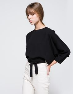 An elegant, lightweight top by Farrow in classic colors with minimal styling. Features round neckline, cropped sleeves, batsleeves, invisible stitching, tie waistband, back matching buttons, open back structure, cropped length and relaxed fit.  •Lightw