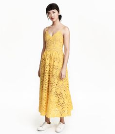 Calf-length dress in lace. V-neck, narrow, adjustable shoulder straps, concealed zip at back, seam at waist with pleats, and full skirt. Jersey lining.
