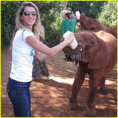 Gisele Bindchen feeding a baby elephant (with her own baby in one arm!)