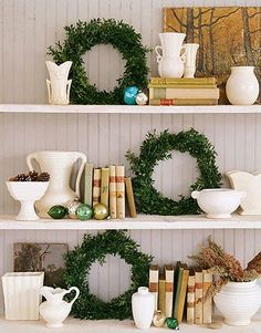 Shelves in living room with miniture wreaths made from boxwood and foam core.