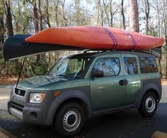 A kayak and a canoe are creatively strapped to the roof rack of a Honda Element.