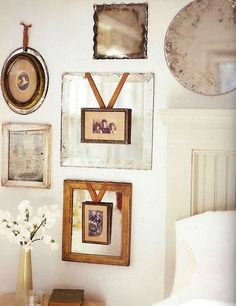 Antique picture frames hung with ribbon over weathered old frames... love this too much.