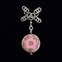 "ery fine Edwardian platinum and gold enamel watch pendantThe pendant watch is decorated with numerous rose cut diamond and pink enamel hanging on a platinum top gold back diamond open work pin Measures 1 1/8"" x 2 3/4"" Weight 15.6 dwt."