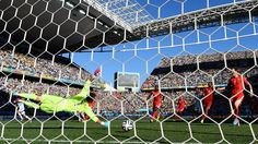 Angel di Maria (1st L) of Argentina scores his team's first goal past Diego Benaglio of Switzerland