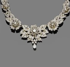 A diamond necklace/tiara combination, circa 1890  Composed of graduating pierced flowerheads and leaves, the largest to the centre, set throughout with old brilliant, single and rose-cut diamonds, with a pear-shaped diamond drop, mounted in silver and gold, tiara frame deficient, central brooch fitting provided, diamonds approx. 5.60ct total, length 37.5cm, fitted case by Nathan & Co, Birmingham by Quella