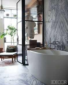 he walls of the master bath are lined with cipollino marble, and the bathtub is by Wetstyle.:
