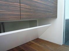 一見壁に見える、洗面台下の収納兼配管隠し扉