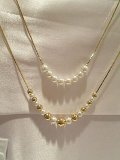 """@ TIER #NECKLACE.  Truly unique combination of simulated pearls and shiny goldtone beads. The upper strand (16"""") has 8 pearls, and the lower strand (20"""") alternates the gold beads and pearls in a graduated design. At your door for only $9.99."""