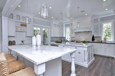 This impressive chefs kitchen has white cabinets and white marble countertops, giving the space a light and airy feel.