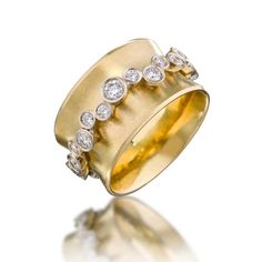 Garland Orbit Ring  18ky/14kw with 1.2 ct diamonds randomly placed in garland orbit.  The 'orbit' revolves freely around concave surface band. Fabricated.