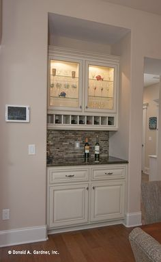 A wet bar is conveniently located by the kitchen, and features glass front cabinetry and wine bottle storage. Kitchen Decor, Kitchen Cabinets, Mini Bar, Bars For Home, Closet Bar, Home, Interior, Kitchen Renovation, Kitchen Wet Bar