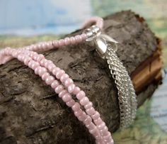 Long Beaded Pink Necklace with Tassel from the Sangha Collection. This necklace includes tiny pale pink glass seed beads strung on wire cord