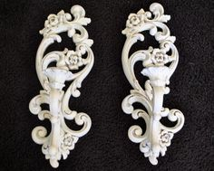 Adorable vintage pair of white shabby upcycled wall hung, sconce style candlestick holders by Homco. Painted by Yours Truly (me) in a neutral white, lightly distressed and sealed with a matte finish. They are designed with a lovely filigree and floral Hollywood Regency motif that Homco is known for. This pair measures 15 tall and 5 1/4 at the widest point. The part that holds the candles sticks out approximately 5 from the wall. the hole that the candle rest is is about 3/4 of an in...