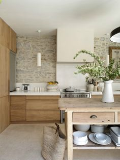 white countertops on wood... stonework on wall with white backsplash... floors match stone, offer mid-tone... simple white architectural exhaust hood... pendant lights... no knobs or pulls! ... i wonder what's behind the stainless steel panel on the left?