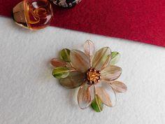 Compoziția florală este confecționată din petale de cuarț rutilat cu aur, mărgele de citrin și hematit. Sârma modelatoare este din cupru placată cu aur de 18 karate
