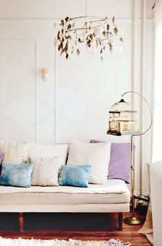 A living room with a white sofa with purple pillows, a bird cage mobile, and a vintage bird cage as decor