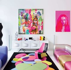 The Vapor floor lamp is by Studio Italia.  The sofas are Karim Rashid's design for Valdichienti, and the Ottawa console is his design for BoConcept.  The rug is a custom Rashid design, made by Oriental Weavers.  The living room features paintings by (from left to right) Ryan McGinness, Jen Mann, and Rashid.  The Sparkle Chair is Rashid's design, a collaboration with LG Hausys.  Photo: Dean Kaufman