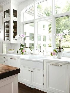 so pretty: orchids, glass corner cabinets, large windows, sink, so fresh!