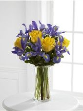 The FTD® Sunlit Treasures™ Bouquet spreads joy and light with its rich display of brilliant color. Deep midnight blue iris set an impressive background to vibrant yellow roses perfectly arranged in a clear glass vase, creating a bouquet of happy wishes fo