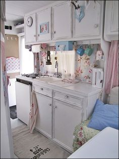 Kitchen in a traveling trailer. So charming. I love the white, light blue and pink colors. Simple and cute.