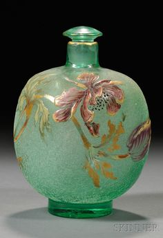 Galle Scent Bottle  Enameled and etched crystal  France, late 19th/early 20th century  Square form with narrow neck and stopper decorated with enameled flowers with gilt highlights on etched green glass, raised on circular foot.