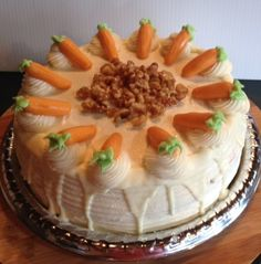 KICKIN' Carrot Cake This Yummy 3 layer cake is super moist and fully loaded with carrots, nuts and pineapple. Filled and topped with cream cheese frosting. Completed with white chocolate drizzle, candied-toasted nuts  and marzipan carrots.