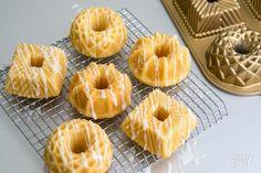 Deze kleine cakejes zijn lekker fris door het gebruik van yoghurt en citroen in het cakebeslag. Het glazuur van limoncello maakt deze mini-tulbandjes echt helemaal af! Natuurlijk kun je ook andere vormpjes gebruiken, bijvoorbeeld een cupcakevorm.  Ingrediënten Voor de cake 150 gr bloem 50 gr amandelmeel 140 gr witte basterdsuiker ¼ tl zout 1 ½ tl bakpoeder 125 gr Griekse yoghurt 3 eieren 1 citroen, rasp ½ citroen, sap 100 gr boter, op kamertemperatuur Verder nodig boter, om in te vetten 100… Sweet Recipes, Cake Recipes, Cupcake Images, Cake Pans, Mini Cakes, High Tea, Muffins, Cake Cookies, Yummy Cakes