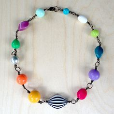 the chakra. a NEW! misfit bauble. $45.00  plump black and white stripey bead along with colors that pop and reflect the chakras ( only represented in the amazing pop of colors. this necklace does not come with chakra power. however, it will make you smile and be happy. i mean look at these colors! )