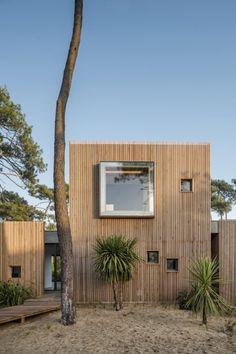 Esta casa, obra del estudio de arquitectura Atelier Delphine Carrere, se encuentra en un gran bosque de pinos, cerca de la playa de Anglet, en la costa atlántica francesa. Los grandes pinos dibujan una línea vertical al igual que el revestimiento de madera de la casa, participando en su inserción en el sitio.