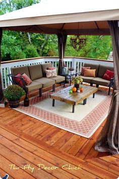 A gazebo creates a relaxing outdoor seating area with two sofas, a coffee table and a candelabra - from Thrifty Decor Chick