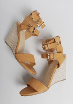 These stylish camel-colored wedges are designed with two adjustable ankle straps, gold-toned hardware, and an espadrille wedge heel.