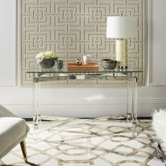 The Lainey Console Table is an exercise in the timeless appeal of good taste. Its gracious design begins with a nod to the classic x-frame style, and evolves into a modern glass, acrylic and brass sculptural masterpiece capable of holding its own. #Console #Table #LivingRoom #Acrylic #SilverAccents #Safavieh