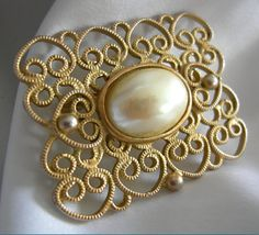 Lightweight Victorian inspired gold tone brooch. Features an oval faux pearl cabochon in the center of gold tone filigree settings. Measures: In