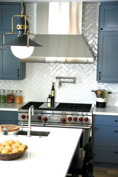 White and blue kitchen features blue cabinets paired with white quartz countertops and white chevron tile backsplash. Kitchen Redo, New Kitchen, Kitchen Remodel, Country Kitchen, Kitchen Ideas, Herringbone Backsplash, Backsplash Tile, Herringbone Pattern, Herringbone Subway Tile