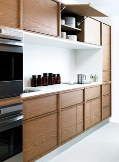 Warm walnut clean lined cabinets with bright white counter top and stainless steel appliances.