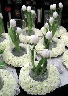 White Tulips in Cylinders that are centered in Wreaths of White Pompom Mums