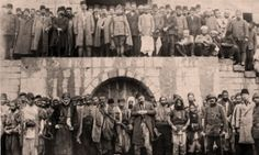Armenians at the Marash army barracks awaiting execution. (Bottom row)  Above them, the Ottoman governor, Haydar Pasha, and soldiers. April 1915.