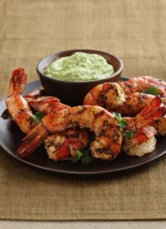 Yield: 8 Servings      Ingredients:    2 limes, juiced and zested  ½ cup roughly chopped fresh cilantro  1 tsp. ground cumin  4 Tbsp. extra-virgin olive oil  2 lbs. large shrimp, peeled and deveined, tails intact  Spicy Hass Avocado Puree (see make-ahead recipe below)  Fresh sprig