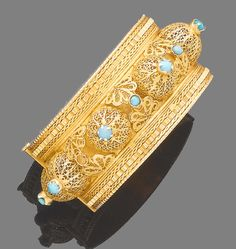 A gold and turquoise bangle  Decorated with gold filigree domes of openwork design, each highlighted with a cabochon turquoise, between ropetwist and plait-link detail